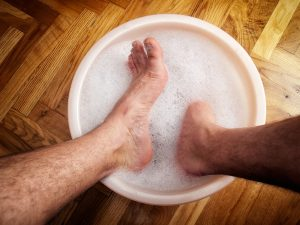 Man soaking his feet in a washbowl before his first visit with Kerryleegh.